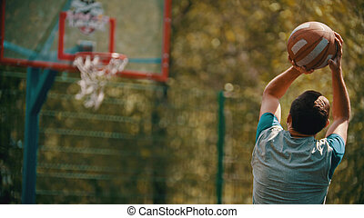 A young man jump and about to throw the ball in the basketball hoop