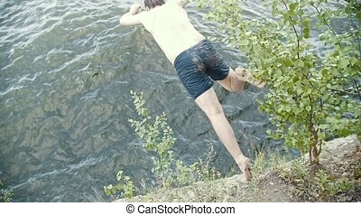 A young man jumps in the river, brave action - slow motion...