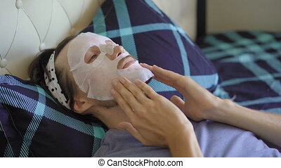 A young man laying on a bed with a cosmetical face mask on his face. Skincare concept.