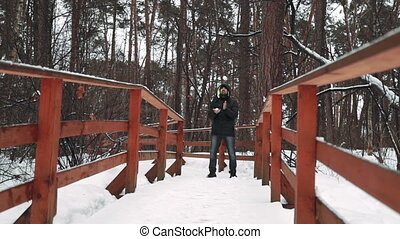 A young man looking at the camera and playing with snow in...