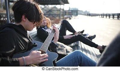 A young man lying on a bench with his friends and playing guitar outdoors