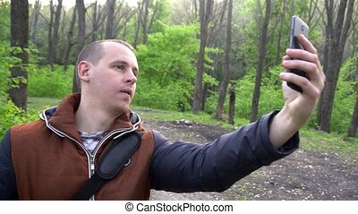 a young man makes a selfie in nature