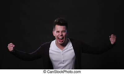 A Young Man Mimicing Against a Black Background - An...