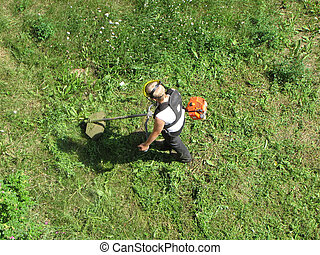 A young man mowing the grass