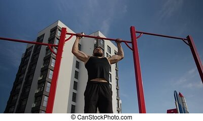 A young man of athletic build pulls up on a red horizontal bar.