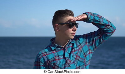 A young man on a background of the sea. Man in sunglasses in sunny weather. Explores the nature around