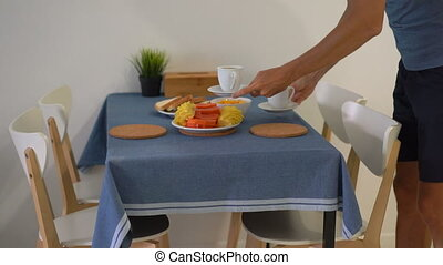 A young man on a kitchen preparing breakfast with fresh tropical fruits for his family