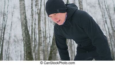 A young man on a morning jog in the winter forest was tired...