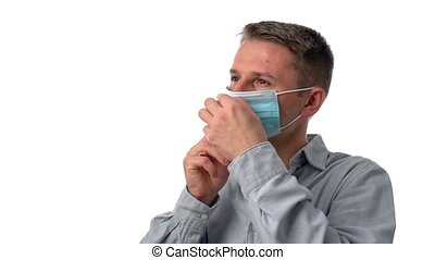 A young man on a white isolated background puts on a surgical mask to protect from allergens and dents. Covid. High quality FullHD footage