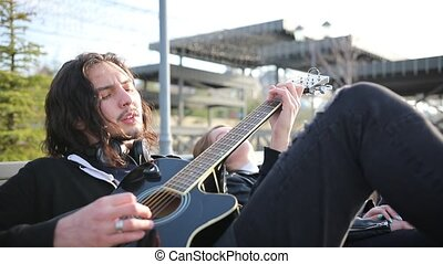 A young man playing guitar and sing