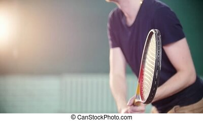 A young man playing tennis indoors. Training