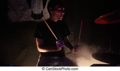 A young man plays drums for a rock band performance