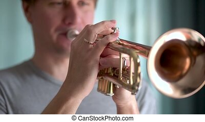 A young man plays the trumpet. Hands close up view