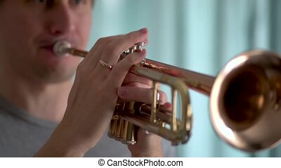 A young man plays the trumpet. Hands of musician. Close up view