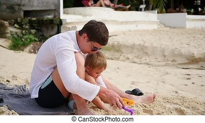 a young man plays with child on the beach. To make the sand molds