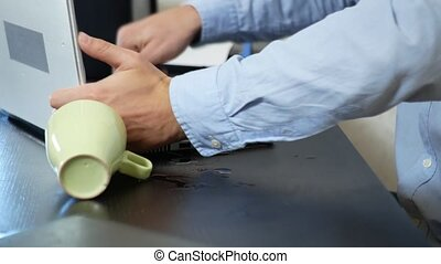 A young man poured tea onto a laptop. works in the office,