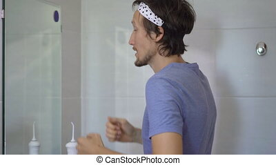 A young man puts on a cosmetical face mask. Skincare concept.