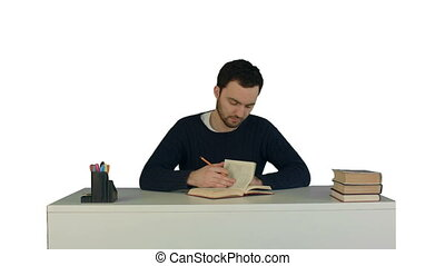 A young man reading a book on laptop on white background isolated