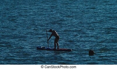 A young man relaxes on a paddle board on a sunny day. 4k,...