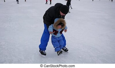 a young man rides on ice and holding a small child