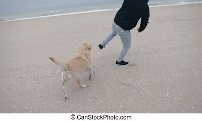 A young man runs along the beach with his dog.