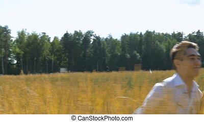 A young man runs to meet his girlfriend. In a wheat field.