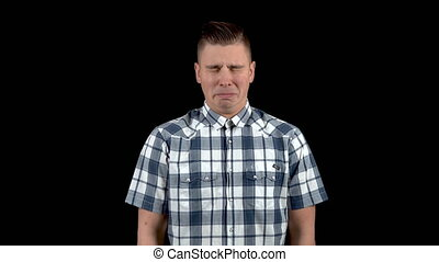 A young man shows an emotion of sadness. Sad man in a shirt on a black background