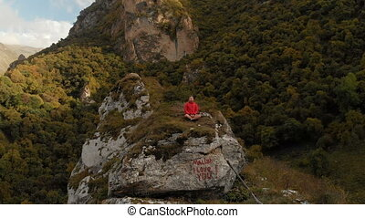 A young man sits in a lotus position on top of a rock in the...