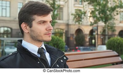 A young man sits on a bench and drinks coffee