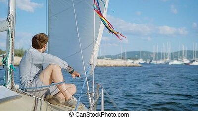 A young man sits on the deck of a yacht that has moved away...