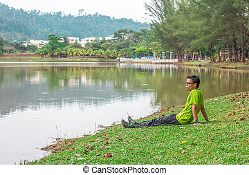 A young man sitting alone near the water