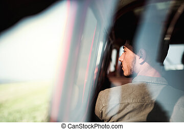 A young man sitting in a car on roadtrip through countryside, shot through glass.