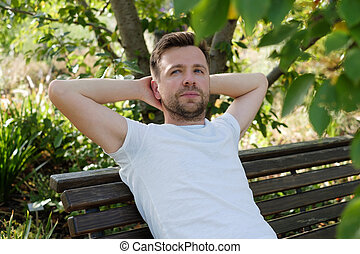 A young man sitting on a bench in the park and having a rest.