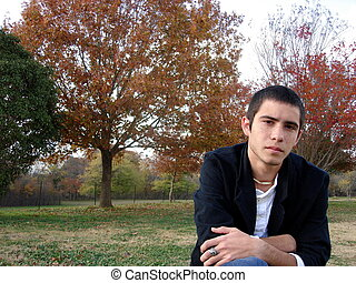 A Young Man Sitting - A yound man sitting on a stump.