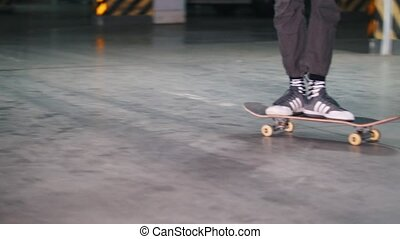 A young man skating in the parking lot and performing tricks