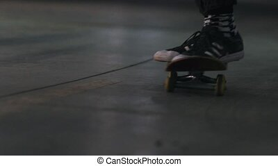 A young man skating in the parking lot. Feet in sneakers....