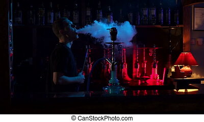 A young man smokes a hookah in a hookah bar on the dark background, slow motion.