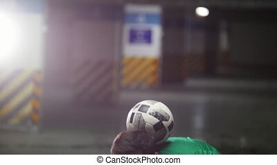 A young man soccer balancing the ball on his head and...
