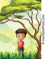 A young man standing at the field near the giant tree