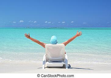 A young man sunbathing on the beach of Exuma, Bahamas