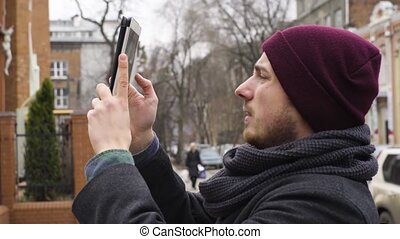 A young man takes a photograph of the church with a tablet