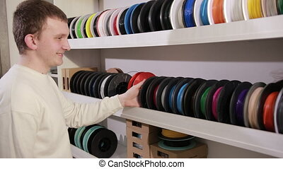 man takes a spool with a plastic thread cable for color ...