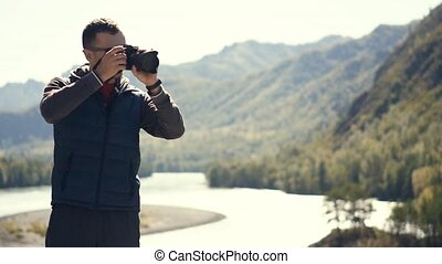 A young man taking photos of the nature of Gorny Altai on his . Slow motion