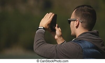 A young man taking photos of the nature of Gorny Altai on his smartphone. Slow motion