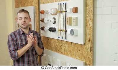 A young man tells and shows the switch sockets and wires of different colors and shapes. Samples are presented on a special stand. Looking at the camera