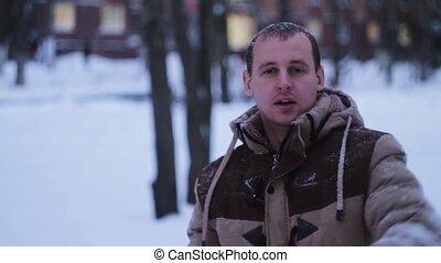 man throws a snowball at the camera
