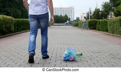 A young man throws out a package of garbage in the center of the city, litterbug