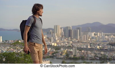 A young man tourist visits the miuntaing overlooking the Nha Trang city, a famous tourist destination in Vietnam.