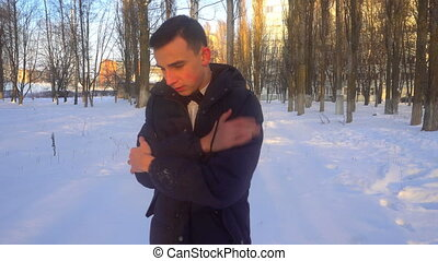 a young man tries to keep warm in winter, standing in the...