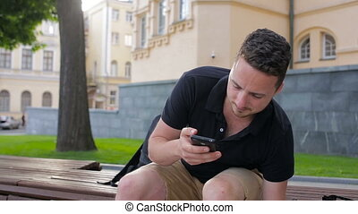 A young man use phone sitting on a bench drinking coffee outside in city